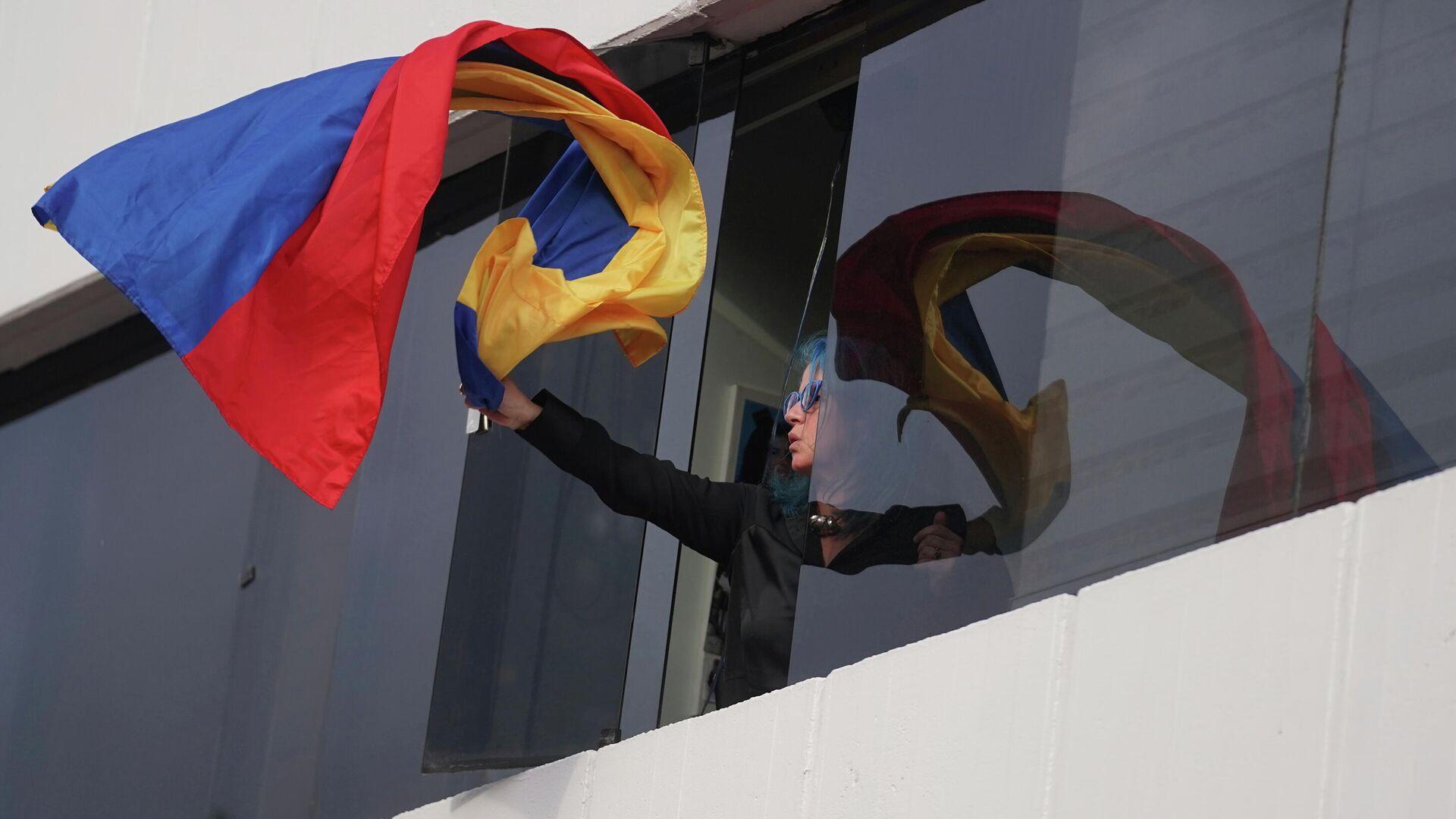 Una mujer saca una bandera de Colombia por la ventana durante las protestas en Colombia - Sputnik Mundo, 1920, 05.05.2021