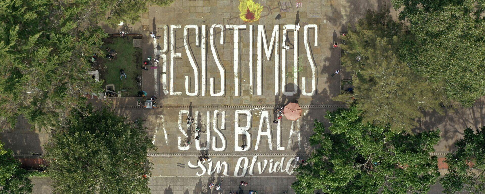 """Vista aérea de personas bloqueando una calle junto a un mensaje que dice """"Resistimos a sus balas sin olvido"""" - Sputnik Mundo, 1920, 10.05.2021"""