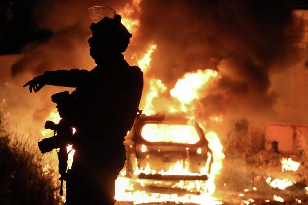 Un policía israelí frente a un coche en llamas durante los enfrentamientos por la posible expulsión de palestinos en beneficio de los colonos israelíes en el barrio de Sheij Jarrah, Jerusalén Este, el 6 de mayo de 2021. - Sputnik Mundo
