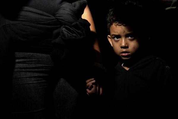 Un niño migrante junto a su madre, que solicita asilo, después de cruzar el río Grande desde México hacia la ciudad de Roma en Texas (EEUU), el 4 de mayo de 2021. - Sputnik Mundo