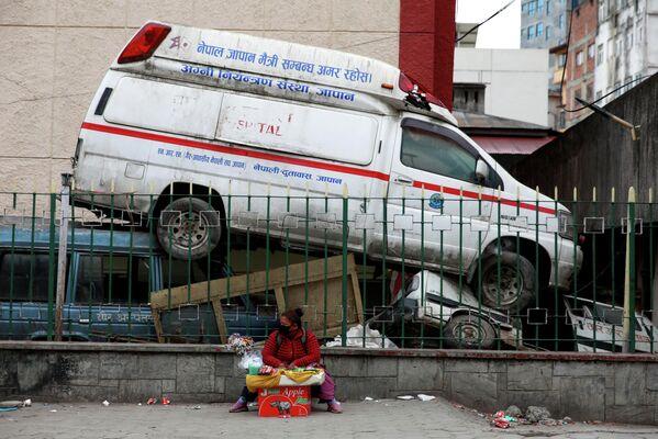 Un vendedor sentado junto a una ambulancia abandonada cerca de un hospital durante la segunda ola de coronavirus en Katmandú (Nepal), el 4 de mayo de 2021. - Sputnik Mundo