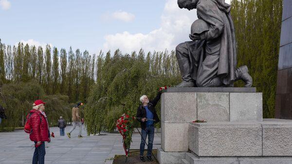 Мужчина возлагает цветы к памятнику советскому солдату на военном мемориале в Трептов-парке в Берлине в ознаменование 76-й годовщины окончания Второй мировой войны - Sputnik Mundo