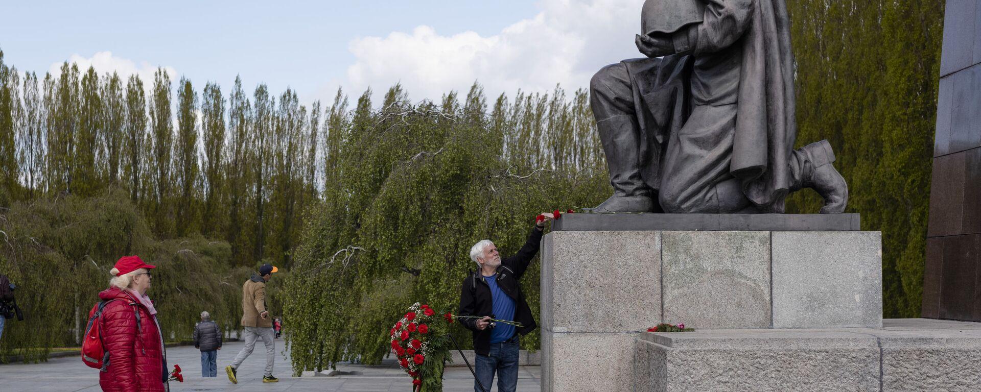 Мужчина возлагает цветы к памятнику советскому солдату на военном мемориале в Трептов-парке в Берлине в ознаменование 76-й годовщины окончания Второй мировой войны - Sputnik Mundo, 1920, 08.05.2021