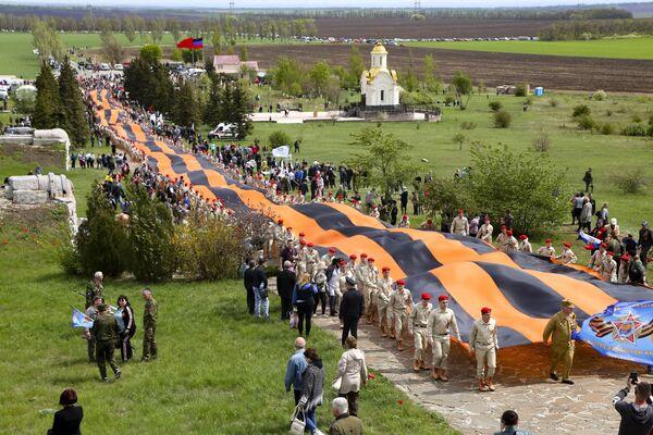 Activistas llevan una cinta de San Jorge de 300 metros, que se ha convertido en un símbolo de la insurgencia prorrusa en el este de Ucrania, a un monumento de la Segunda Guerra Mundial en el montículo de Saur-Mogila, a unos 60 km al este de Donetsk.  - Sputnik Mundo