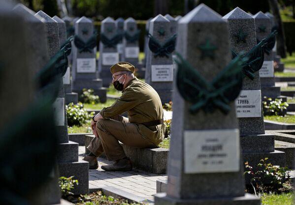 Un hombre rinde honores frente a las tumbas de soldados rusos en el cementerio de Olsany (Praga) para conmemorar el 76 aniversario del fin de la Segunda Guerra Mundial. - Sputnik Mundo
