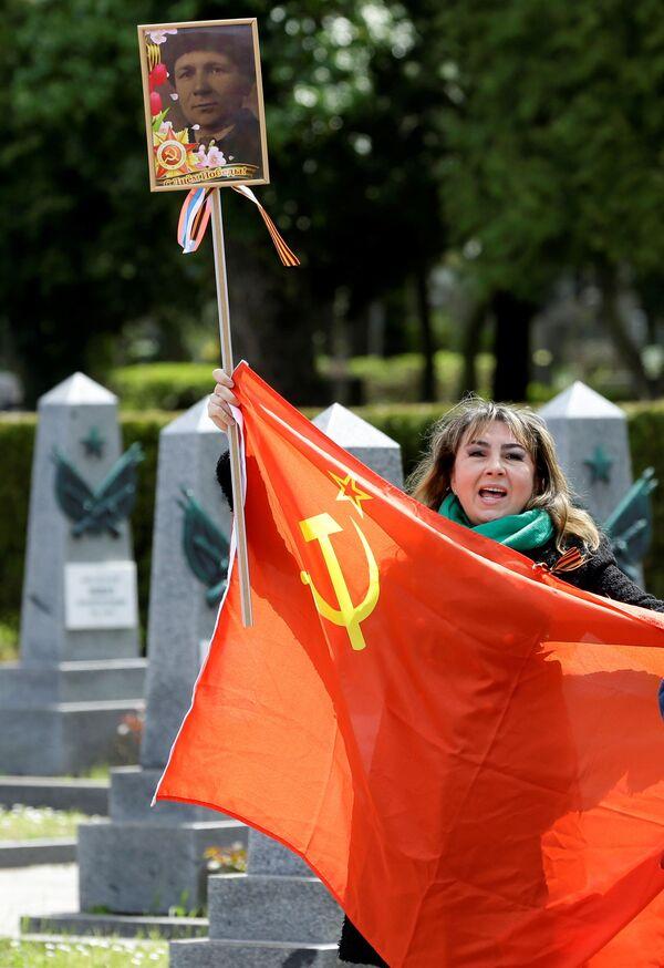 Una mujer sostiene una bandera y canta frente a las tumbas de soldados rusos en el cementerio de Olsany, en la capital de la República Checa, para conmemorar el 76 aniversario del fin de la Segunda Guerra Mundial.   - Sputnik Mundo