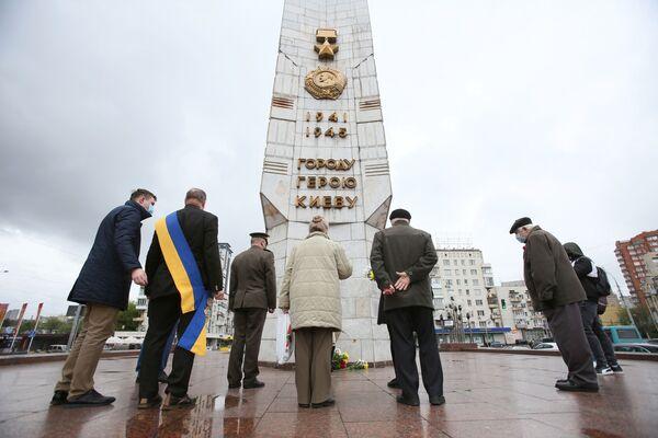 Las personas depositan flores frente al obelisco de la Ciudad Heróica de Kiev en la plaza de la Victoria de la capital ucraniana. - Sputnik Mundo