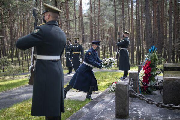 Los soldados lituanos de la guardia de honor, que llevan mascarillas para prevenir la propagación del coronavirus, depositan una ofrenda floral durante la ceremonia con motivo del 76 aniversario del fin de la Segunda Guerra Mundial en el memorial Paneriai, en la capital de Lituania.  - Sputnik Mundo