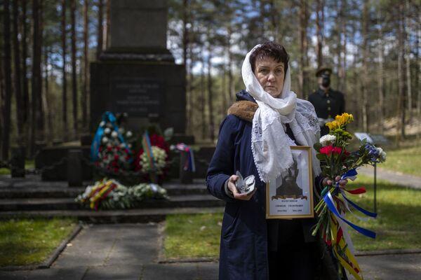 Una mujer sostiene un retrato de un familiar que participó en la Segunda Guerra Mundial durante una ceremonia con motivo del 76 aniversario del fin de la Segunda Guerra Mundial en el memorial Paneriai.  - Sputnik Mundo