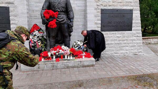 El sacerdote de las Fuerzas Armadas de Estonia deposita una ofrenda floral frente al Monumento a los caídos durante la Segunda Guerra Mundial (también conocido como el Soldado de Bronce o el Monumento a los Libertadores de Tallin) en un cementerio militar de Tallin.   - Sputnik Mundo