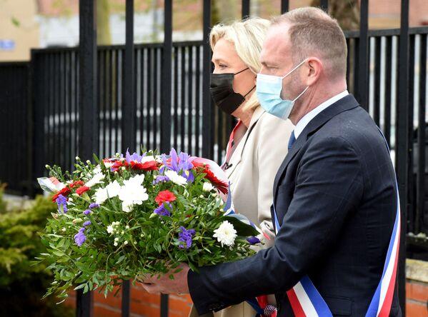 La presidenta del partido de derecha francés Agrupación Nacional y miembro del Parlamento, Marine Le Pen, y el alcalde de Hénin-Beaumont, Steeve Briois, depositan una ofrenda floral para conmemorar el 76 aniversario del fin de la Segunda Guerra Mundial en Hénin-Beaumont, al este de Francia. - Sputnik Mundo