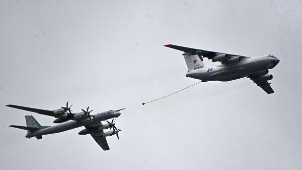 El avión cisterna Il-78 y el bombardero portamisiles estratégico Tu-95 muestran un reabastecimiento aéreo sobre la Plaza Roja.  - Sputnik Mundo