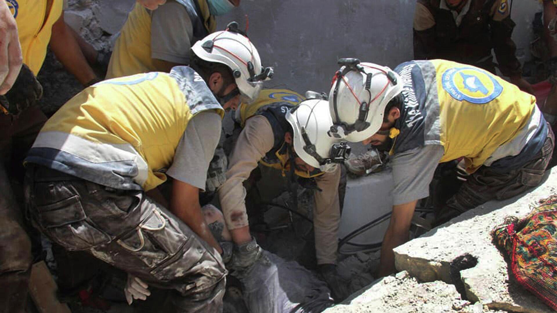Unos Cascos Blancos sacan a una víctima de debajo de los escombros de un edificio destruido por un ataque aéreo en Siria - Sputnik Mundo, 1920, 10.05.2021