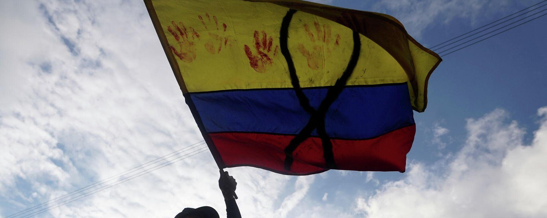 Un manifestante con una bandera de Colombia con un lazo negro y manchas rojas - Sputnik Mundo, 1920, 31.05.2021