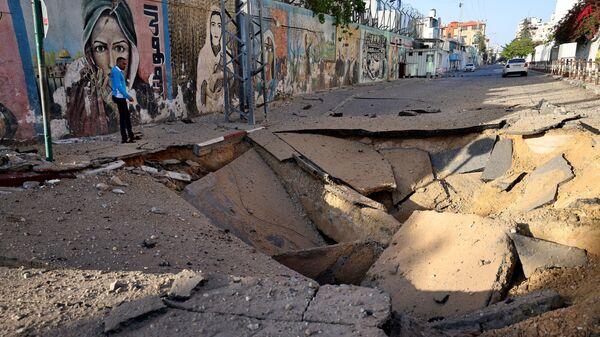Палестинец стоит перед огромной воронкой в городе Газа - Sputnik Mundo