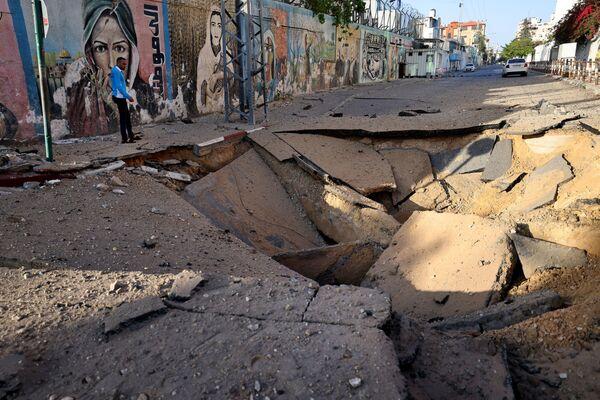 En el lugar del impacto de un proyectil israelí en la Franja de Gaza.  - Sputnik Mundo