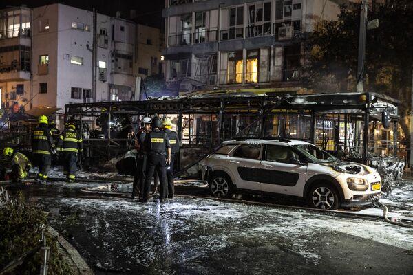 Poco después de la destrucción del edificio, los grupos palestinos dijeron que respondieron con 130 cohetes contra Tel Aviv. En la foto: los bomberos en el lugar donde impactó un cohete palestino en la ciudad de Holon, cerca de Tel Aviv.  - Sputnik Mundo