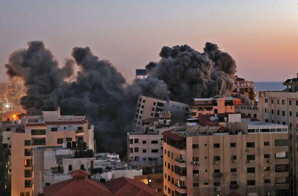 Según las Fuerzas de Defensa de Israel, desde el 10 de mayo por la noche se han disparado más de 1.000 cohetes y granadas de mortero desde la Franja de Gaza contra ciudades israelíes. Las Fuerzas de Defensa Israelí (FDI) respondieron atacando unos 500 objetivos. En la foto: los apartamentos en la Franja de Gaza que se incendiaron tras los ataques aéreos israelíes.  - Sputnik Mundo