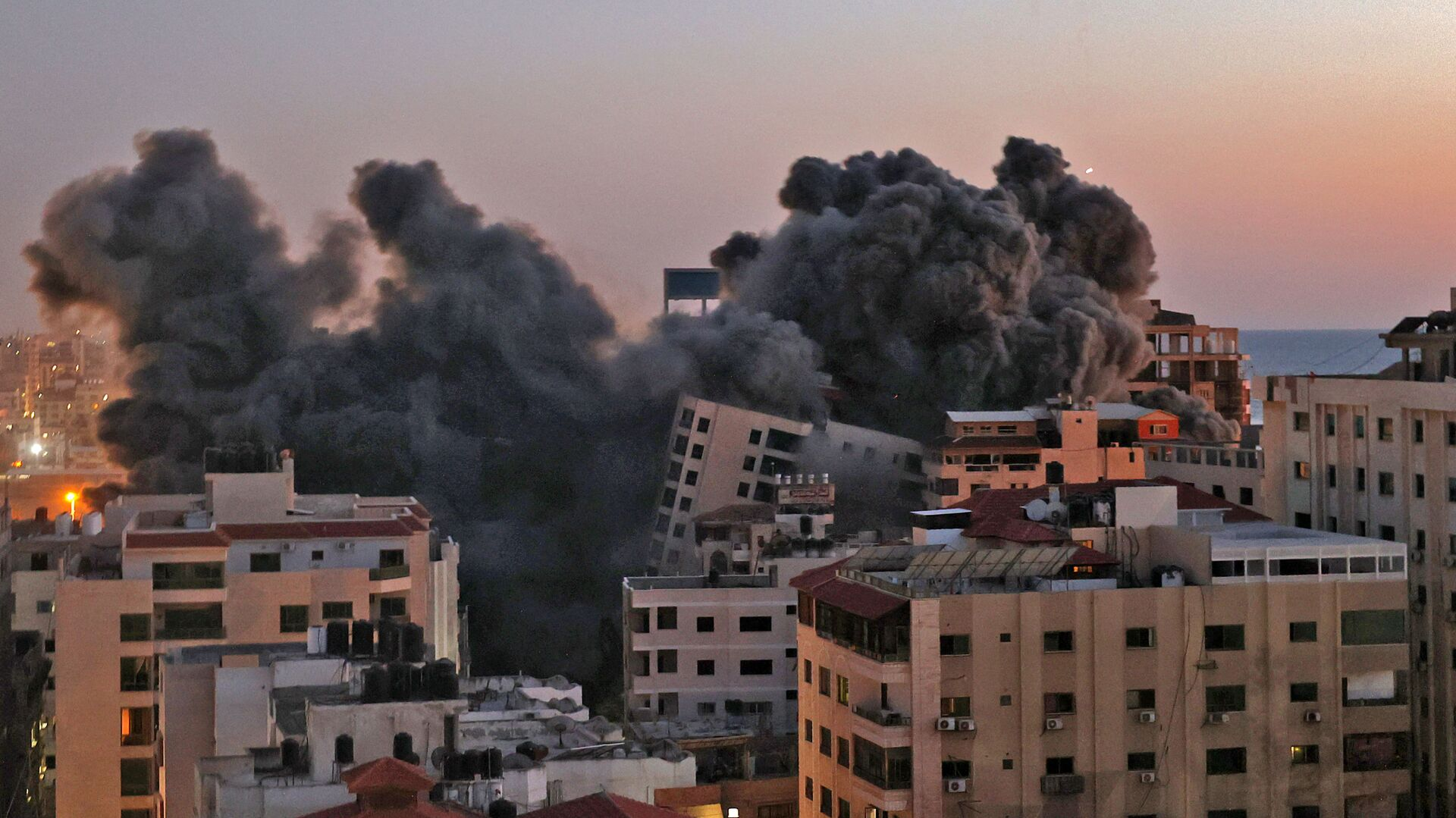 Пожарные тушат горящие многоквартирные дома после израильских авиаударов в городе Газа - Sputnik Mundo, 1920, 20.05.2021