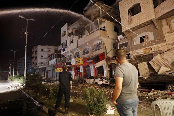En la Franja de Gaza se reportó que los aviones israelíes bombardearon edificios gubernamentales, incluido el Ministerio del Interior. En la foto: los bomberos apagan las viviendas que se incendiaron como consecuencia de los ataques aéreos israelíes.  - Sputnik Mundo