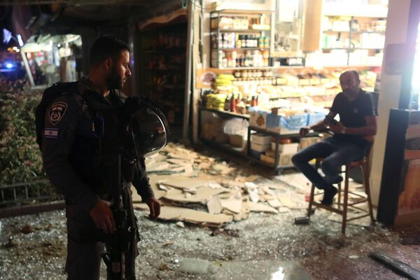 Un funcionario de seguridad israelí habla con un testigo del impacto de un cohete palestino en Holon.  - Sputnik Mundo