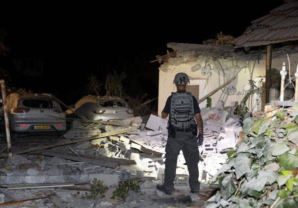 """La ONU expresó su """"grave preocupación"""" por la escalada del conflicto. Las autoridades egipcias dijeron que habían tratado de impulsar un alto el fuego, pero la violencia ya había cobrado un """"impulso imparable"""". EEUU, Reino Unido, Turquía y la mayoría de los países árabes protestaron por la escalada de violencia. En la foto: un oficial israelí frente a una casa destruida en la ciudad de Yehud, cerca de Tel Aviv.  - Sputnik Mundo"""