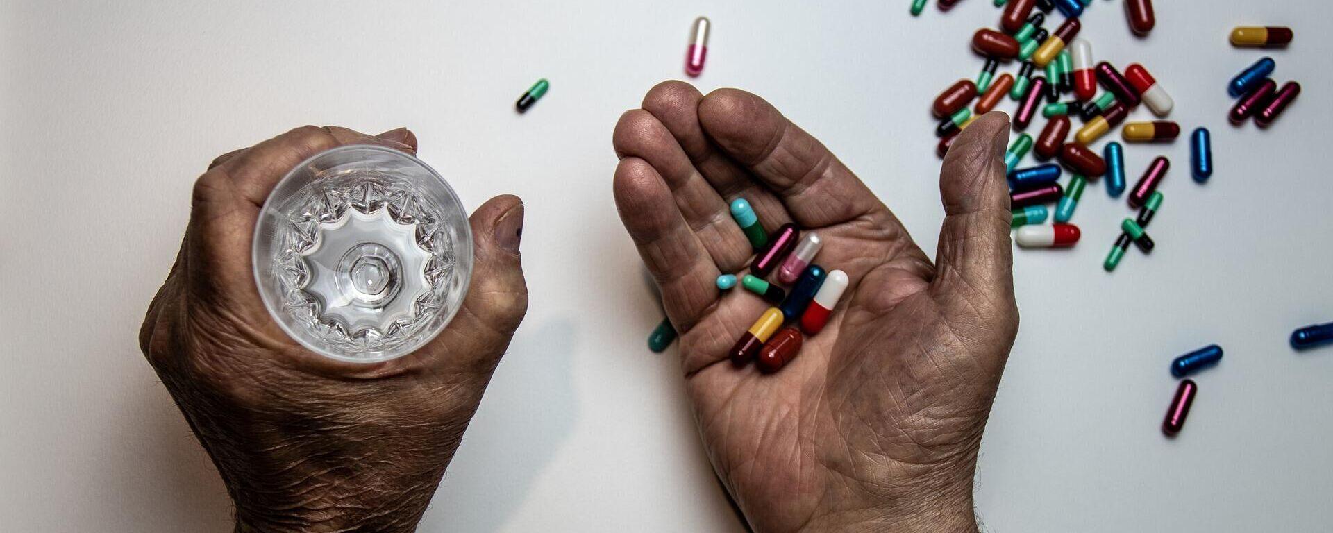 Una persona a punto de tomar píldoras - Sputnik Mundo, 1920, 12.05.2021
