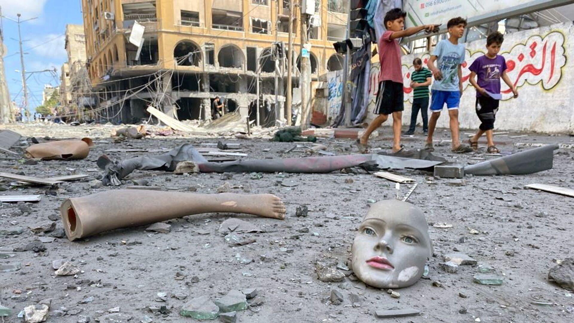 Части сломанного манекена лежат на земле возле здания, пострадавшего от ударов израильской авиации во время вспышки израильско-палестинского конфликта, Газа - Sputnik Mundo, 1920, 16.05.2021