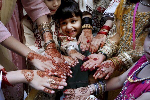 Unas mujeres musulmanas muestran las manos pintadas con alheña —un tinte natural rojizo típico de algunos países árabes— en honor al Eid al-Fitr en Peshawar (Pakistán).  - Sputnik Mundo