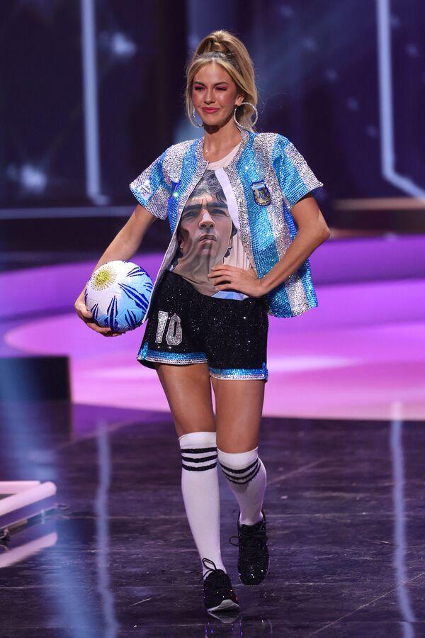 La participante de Argentina, Alina Akselrad, rindió homenaje al mítico futbolista Diego Maradona, fallecido en noviembre de 2020: la mujer subió al escenario vestida con el uniforme de la selección albiceleste y una camiseta con el retrato del 'Diez'. - Sputnik Mundo