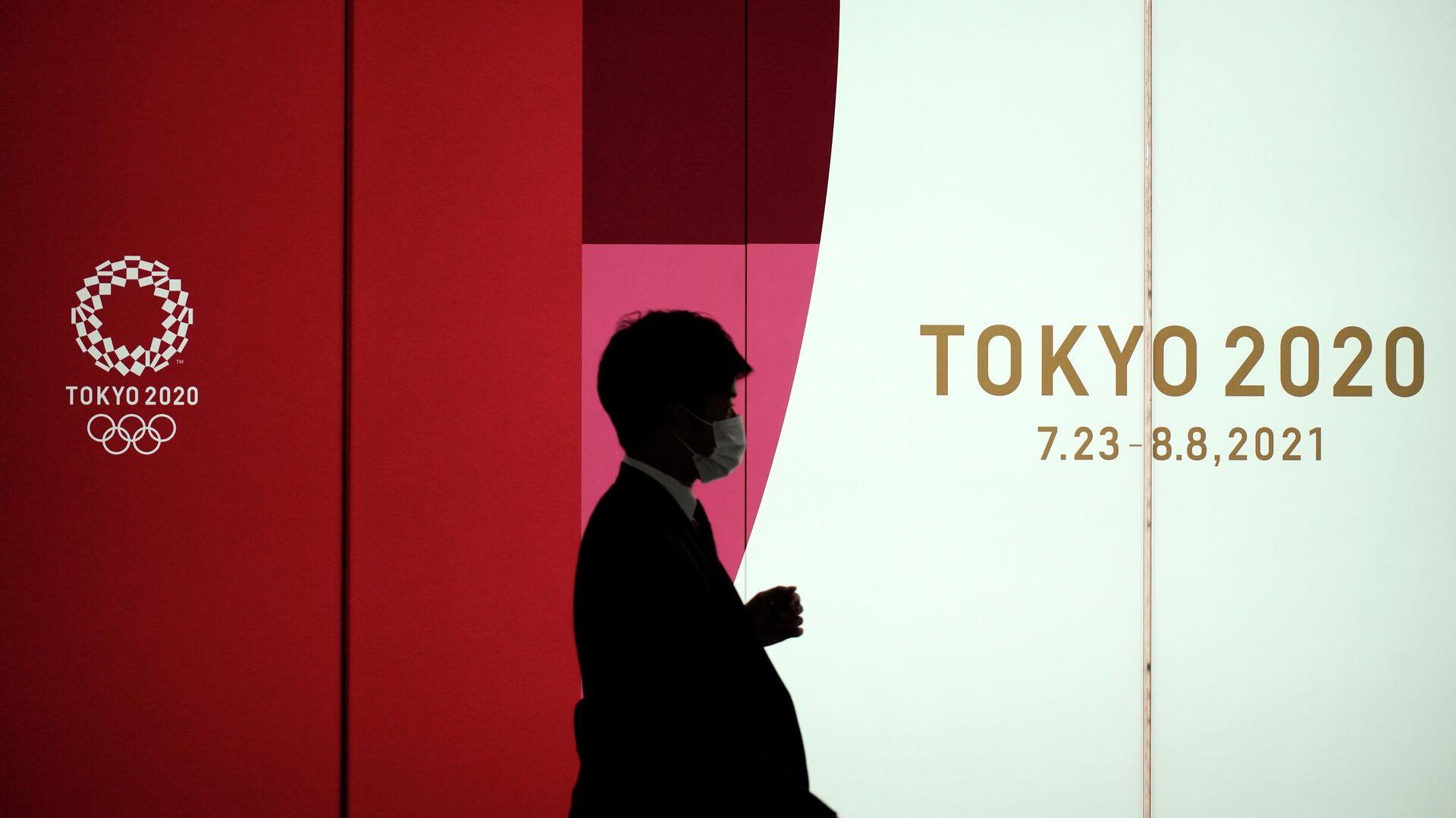 Un hombre camina junto a una pared de los Juegos Olímpicos de Tokio 2020 - Sputnik Mundo, 1920, 14.05.2021