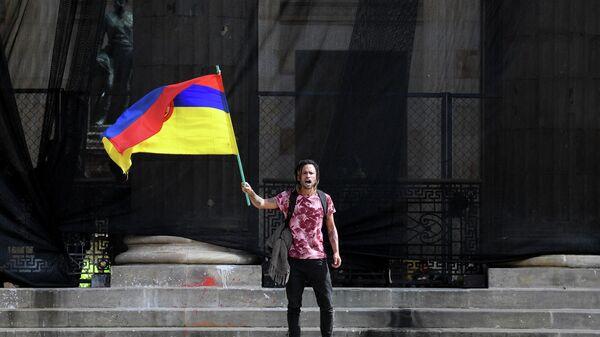 Un hombre con la bandera de Colombia del revés - Sputnik Mundo