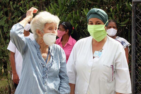 La doctora Ritcey Rosales acompaña a una voluntari de la tercera edad - Sputnik Mundo