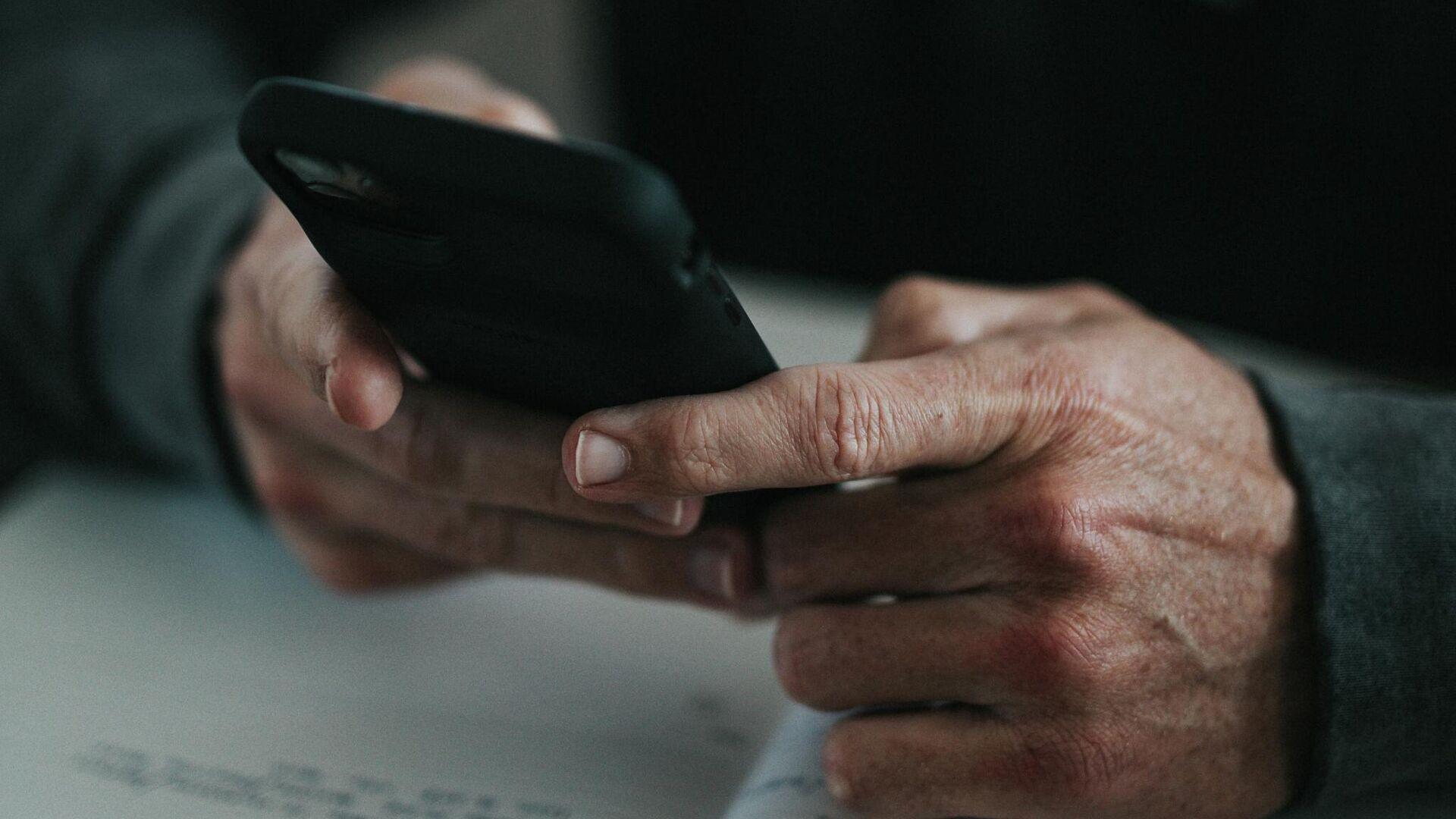 Una persona con un teléfono en sus manos - Sputnik Mundo, 1920, 27.08.2021