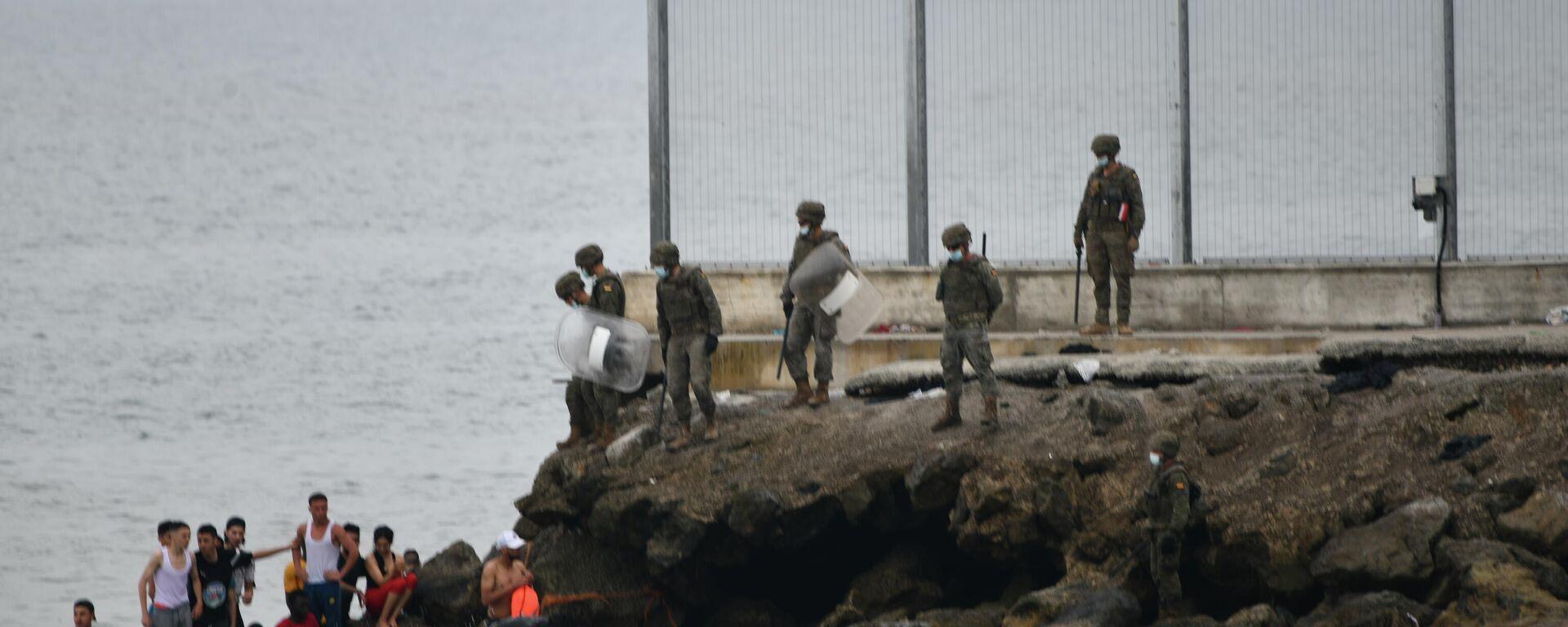 Militares del ejército español vigilan durante las devoluciones en caliente que están efectuando a los migrantes que han entrado en Ceuta procedente de Marruecos - Sputnik Mundo, 1920, 19.05.2021
