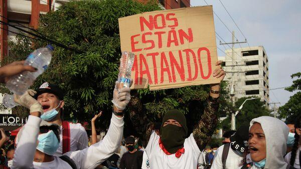 Un manifestante sostiene una pancarta que dice 'nos están matando' frente al estadio Romelio Martínez en Barranquilla. 13 de mayo de 2021 - Sputnik Mundo