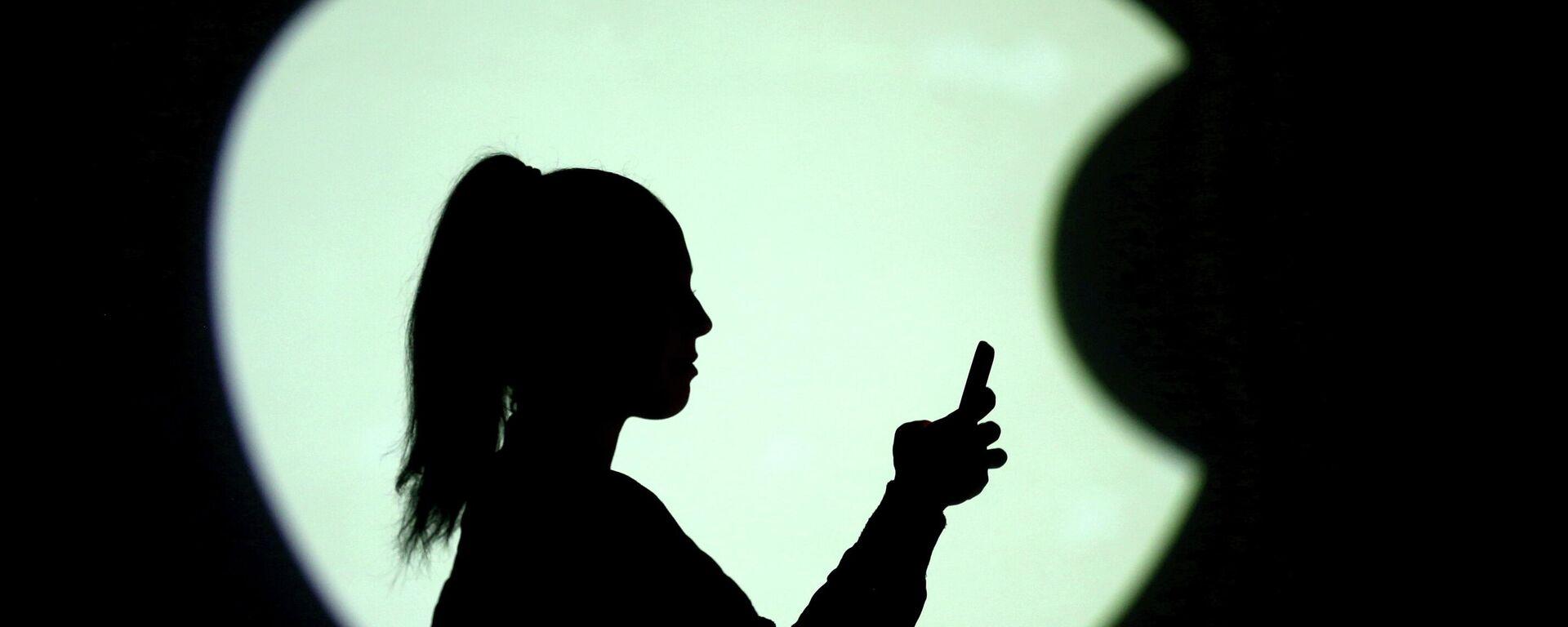 Una persona con un teléfono en el fondo del logo de Apple - Sputnik Mundo, 1920, 19.05.2021