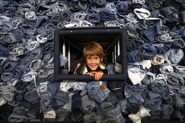 Los primeros jeans fueron producidos y vendidos en 1850 por Levi Strauss, quien emigró a Estados Unidos desde Alemania tres años antes. Los primeros pantalones se hicieron de lona y tenían muchos bolsillos.En la foto: Un niño posa al lado de 33.088 pares de jeans recolectados por la revista National Geographic Kids para ser reciclados y convertidos en material aislante para viviendas en Washington. - Sputnik Mundo