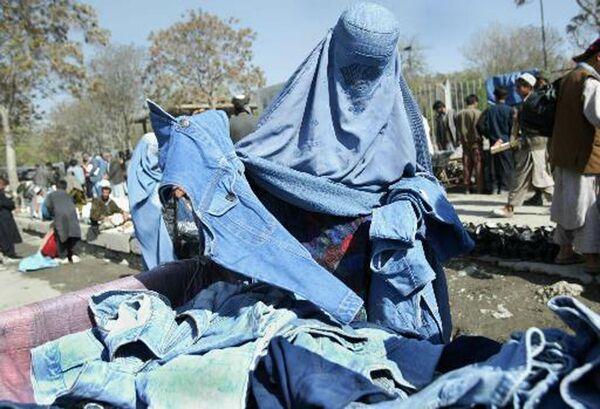 La demanda por los pantalones crecía día a día. Pronto, el migrante alemán fundó la empresa Levi Strauss & Co para fabricar ropa para los trabajadores.En la foto: una mujer afgana compra jeans en un mercado callejero en Kabul, 2003. - Sputnik Mundo