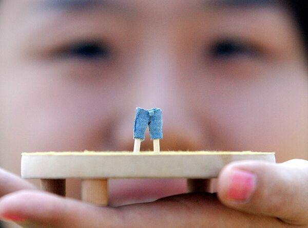 El 20 de mayo de 1873, la compañía recibió una patente de sus pantalones jeans. Este día se considera el día oficial del nacimiento de los vaqueros.En la foto: un empleado de la tienda Levi's Jeans en Corea del Sur muestra los más pequeños vaqueros del mundo. - Sputnik Mundo