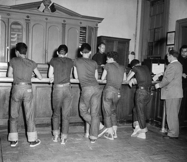 En los años 50, los jeans azules fueron prohibidos en ciertos lugares como escuelas, teatros y restaurantes de Estados Unidos porque eran vistos como una forma de rebelión contra el conformismo.En las fotos: unos jóvenes sospechosos de delincuencia en una comisaría de policía de Nueva York, 1959.  - Sputnik Mundo