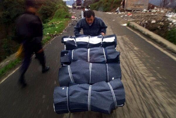 En 2020, el valor del mercado mundial de jeans se estimó en 110.250 millones de dólares.En la foto: un hombre empuja un carrito lleno de piezas para la fabricación de jeans de la marca Guess en Teziutlán, México. - Sputnik Mundo