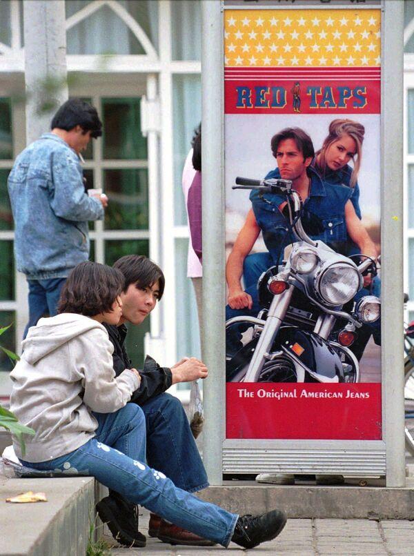 Pese a que surgió en EEUU, el país líder mundial en las importaciones de vaqueros es China.En la foto: unos adolescentes chinos cerca de una cabina telefónica con un anuncio de moda vaquera en Pekín, 1995.  - Sputnik Mundo