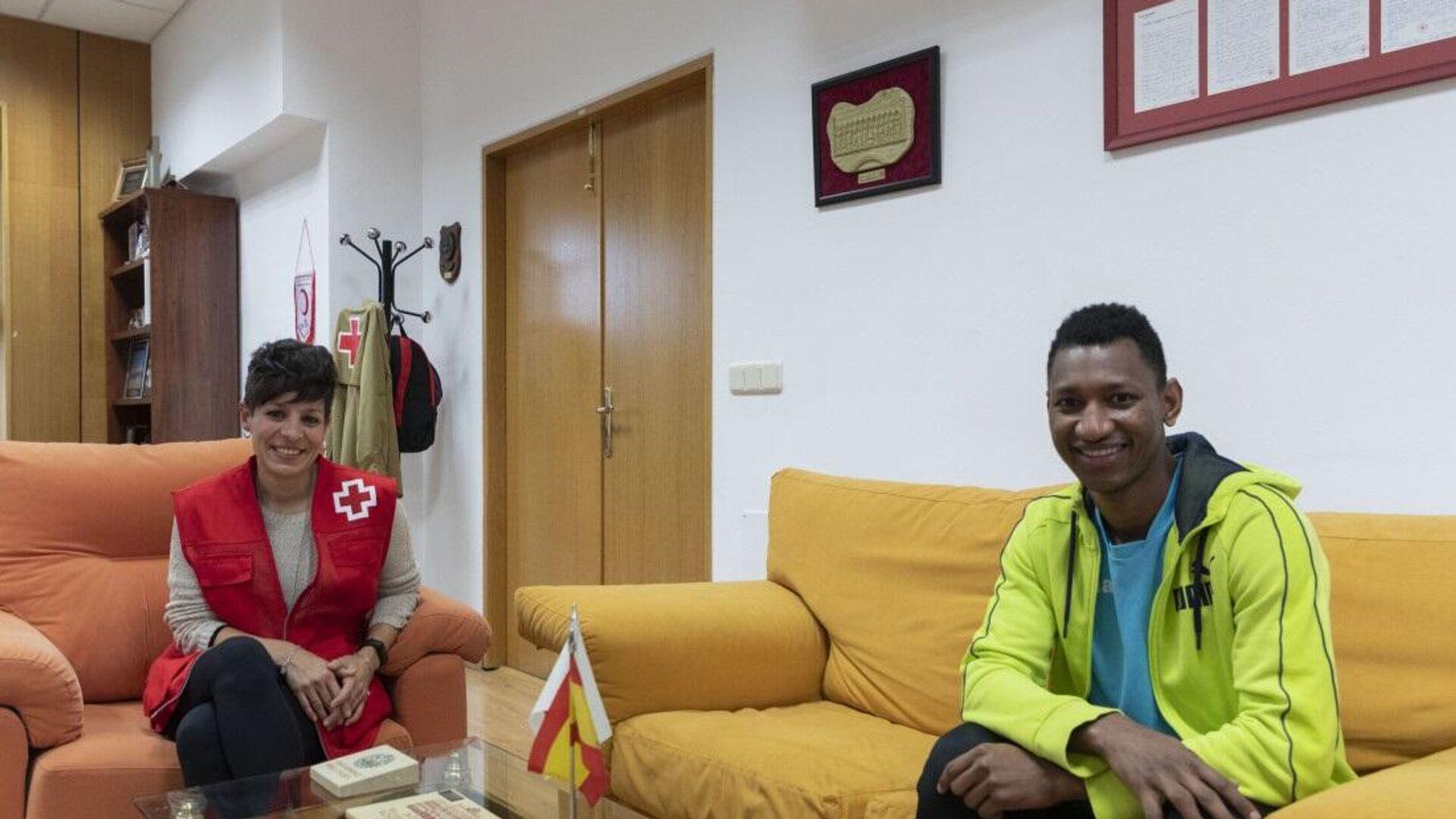 A la derecha, Mamadú, joven guineano de 19 años, en el piso de emancipación de Cruz Roja donde reside. A su lado, Yohana Martín, responsable de la ONG - Sputnik Mundo, 1920, 20.05.2021