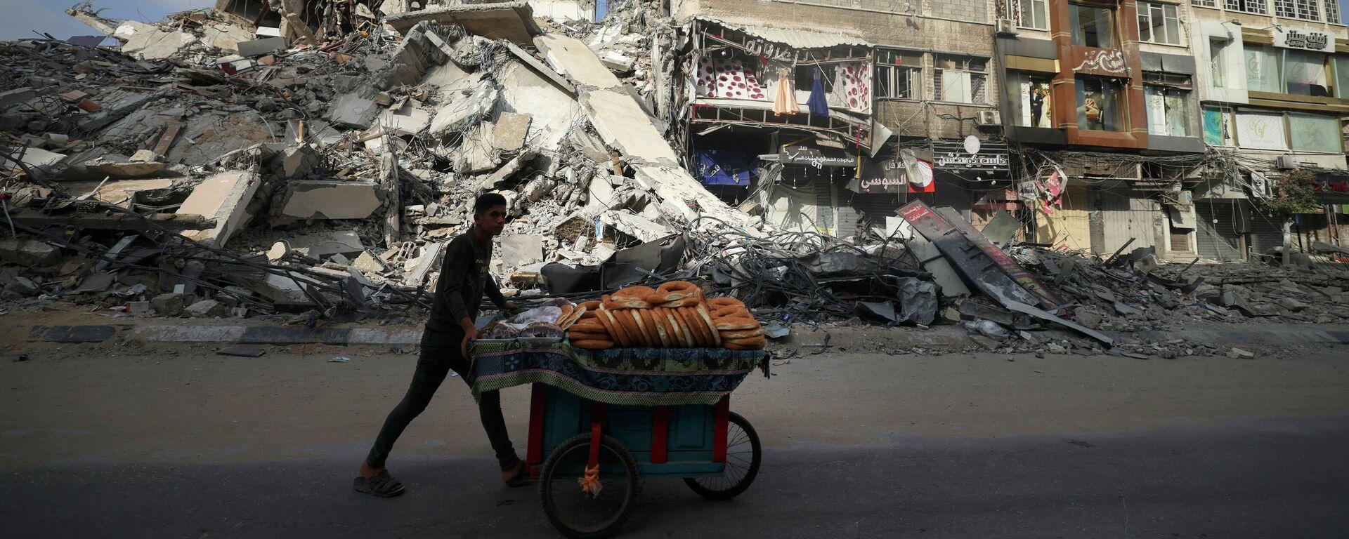 Un palestino camina al lado de un edificio destruido en Gaza tras los bombardeos israelíes - Sputnik Mundo, 1920, 21.05.2021