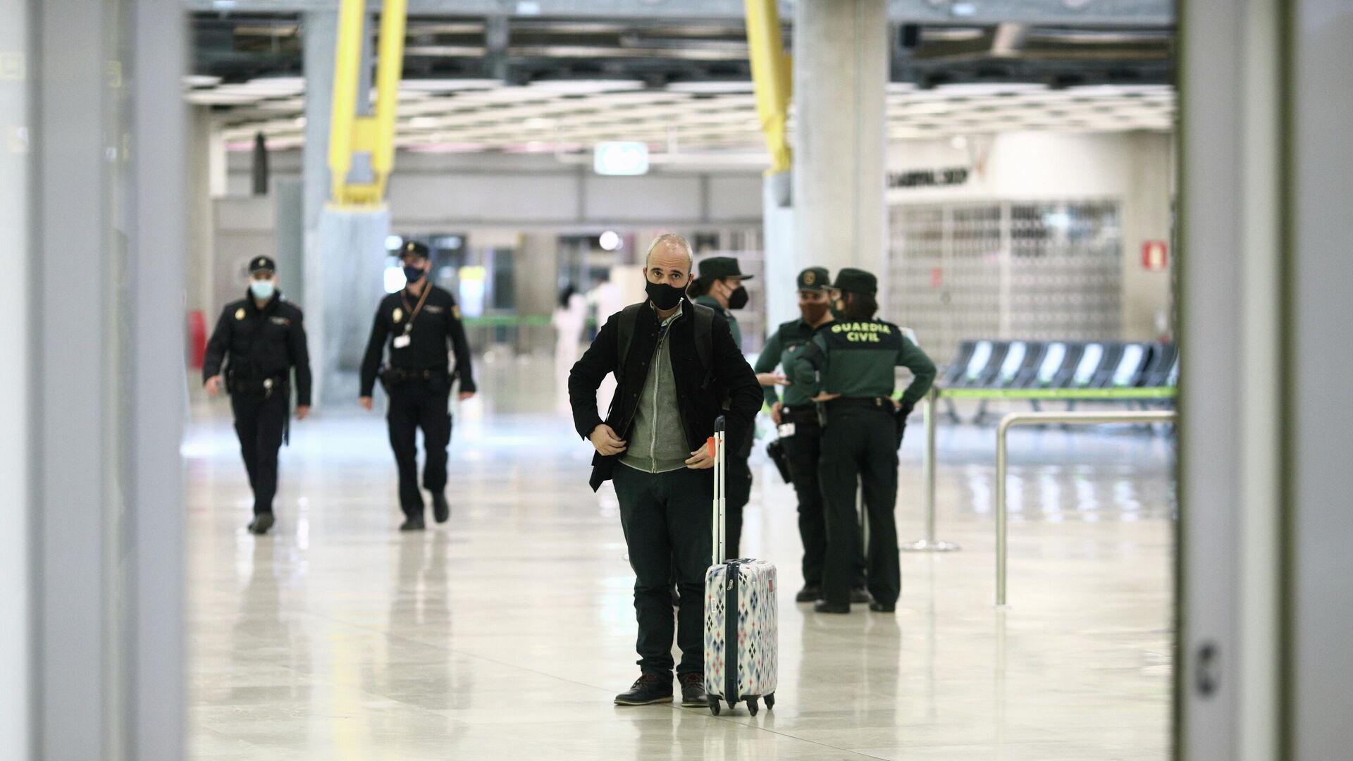 Un pasajero con maleta junto a agentes de la Guardia Civil en la terminal T4 del Aeropuerto de Madrid-Barajas Adolfo Suárez, en Madrid - Sputnik Mundo, 1920, 21.05.2021