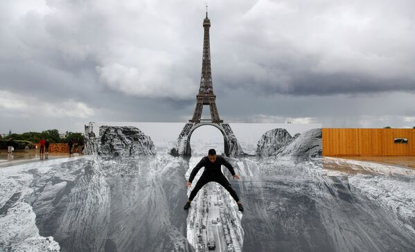 Un hombre posa sobre el gigantesco 'collage' del artista francés JR en la plaza del Trocadero, frente a la Torre Eiffel en París (Francia).  - Sputnik Mundo