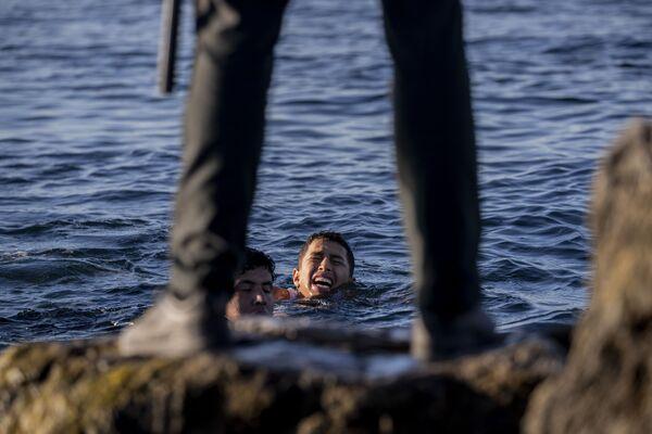 Un representante de la Guardia Civil española con unos inmigrantes en la costa de Ceuta, cerca de la frontera hispano-marroquí.  - Sputnik Mundo
