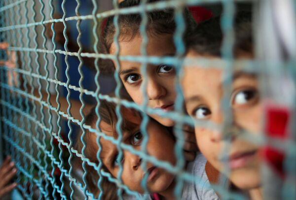 Varios niños palestinos que abandonaron sus casas por los ataques israelíes en una escuela de la ONU en Gaza.  - Sputnik Mundo