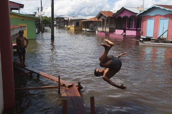 Un chico salta al agua en una calle inundada en el estado de Amazonas (Brasil).  - Sputnik Mundo